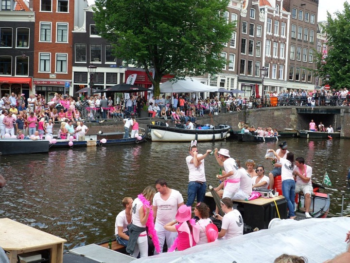 People gather for the Amsterdam Pride parade on the canal outside Anne Frank's house